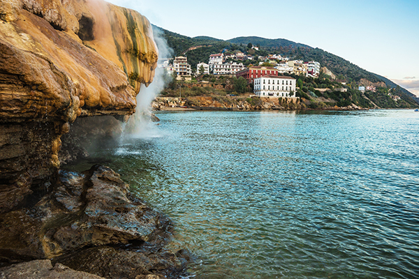 Scenic thermal waterfalls and rock formations on the beach in Loutro Edipsou, Evia, Greece